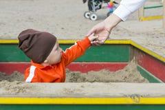 Le petit enfant dans le bac à sable donne le sable Photo stock