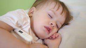 Le petit enfant dort dans la salle d'hôpital sur la température blanche de literie et de mesures avec le thermomètre Traitement d clips vidéos