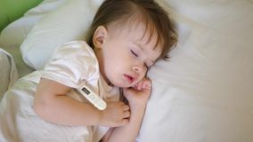 Le petit enfant dort dans la salle d'hôpital sur la température blanche de literie et de mesures avec le thermomètre Traitement d banque de vidéos