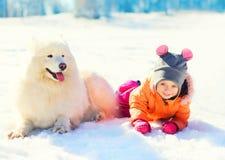Le petit enfant et le Samoyed blanc poursuivent le mensonge le jour d'hiver de neige Photographie stock