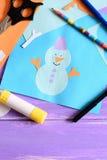 Le petit enfant a fait une carte de papier avec un bonhomme de neige, flocons de neige et les mots I aiment l'hiver Ciseaux, bâto Photo libre de droits
