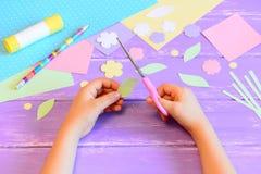 Le petit enfant fait une carte de voeux pour la maman L'enfant juge des ciseaux disponibles et coupe une feuille de papier opérat Photos stock