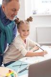 Le petit enfant habile peint avec le grand-parent Photographie stock libre de droits