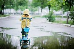 Le petit enfant heureux dans un imperméable jaune monte un scooter à travers le magma image libre de droits