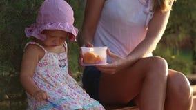 le petit enfant mange des fruits avec la fourchette hors de la gamelle banque de vidéos