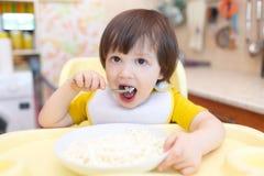 Le petit enfant mange le quark avec la crème sure sur la cuisine Photographie stock libre de droits