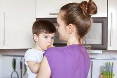 Le petit enfant masculin attirant mange de la pâtisserie, regard pensivement, étant sur des mains du ` s de mère, se tiennent ens images stock