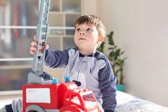 Le petit enfant masculin espiègle joue dans la chambre à coucher avec la voiture de jouet, a concentré le regard, aspect agréable images stock