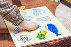 Le petit enfant met le puzzle simple sur le plancher Photos stock