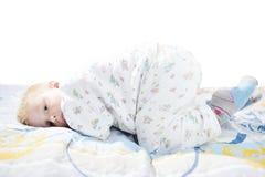 Le petit enfant mignon drôle dans des pyjamas avec les cheveux blonds se trouve sur un lit Images libres de droits