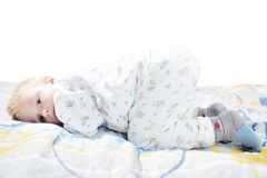 Le petit enfant mignon drôle dans des pyjamas avec les cheveux blonds se trouve sur un lit Photo stock