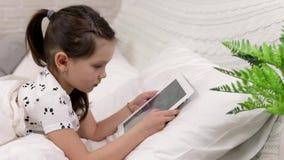 Le petit enfant mignon que la fille se situe dans le lit utilise le comprim? num?rique clips vidéos