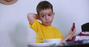 Le petit enfant mignon s'assied à la table et mange sa propre farine d'avoine, et mange du fruit exotique, le bébé mange volontai banque de vidéos