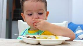 Le petit enfant mignon s'assied à une table dans un bavoir et mange de sa propre purée, le bébé mange volontairement Petite conso clips vidéos
