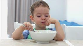 Le petit enfant mignon s'assied à une table et mange sa propre farine d'avoine, le bébé mange volontairement Enfance heureux de c clips vidéos