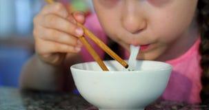 Le petit enfant mignon s'assied à une table et mange ses nouilles, le bébé mange volontairement Peu fille mangeant des nouilles a clips vidéos