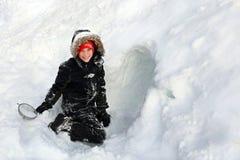 Le petit enfant mignon tout empaqueté pour l'hiver construit un tunnel dans une pile de neige photographie stock libre de droits