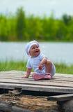 Le petit enfant rit fort sur le plancher de bois de construction Image stock
