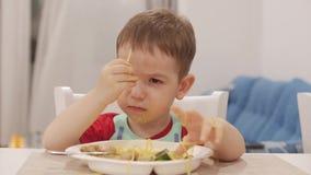 Le petit enfant s'assied à une table dans un bavoir et mange ses propres spaghetti, le bébé mignon mange volontairement Petite ch banque de vidéos