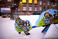 Le petit enfant secoue sur l'oscillation au terrain de jeu en hiver Photographie stock libre de droits