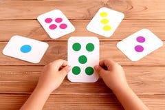 Le petit enfant tient une carte de formation ses mains et en apprenant la couleur, forme, quantité Cartes flash colorées pour l'e Images stock