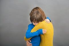 Le petit enfant triste, garçon, étreignant sa mère à la maison, a isolé l'imag photo stock