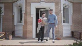 Le petit-fils adulte et son bouquet de participation de grand-mère des tulipes donnent sur le porche de la grande maison Le dire  banque de vidéos
