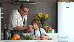 Le petit-fils et le grand-père font cuire ensemble dans la cuisine Un homme plus âgé donne pour juger un garçon de salade Style d banque de vidéos