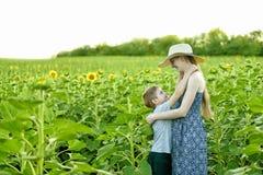Le petit fils heureux embrasse la position enceinte de m?re sur un champ des tournesols de floraison images libres de droits
