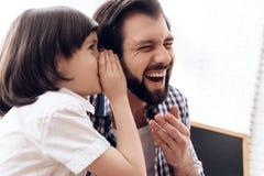 Le petit fils parle dans l'oreille du père une plaisanterie drôle images libres de droits