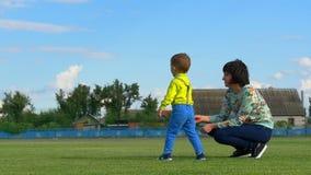 Le petit fils souffle des bulles de savon au soleil avec sa jeune mère dehors banque de vidéos
