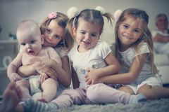 Le petit frère de bébé avec des soeurs pose à l'appareil-photo Images libres de droits