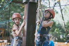 Le petit frère et la soeur font s'élever en parc d'aventure photo libre de droits