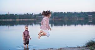 Le petit frère et la soeur ont l'amusement près de la rivière Enfance heureux photographie stock