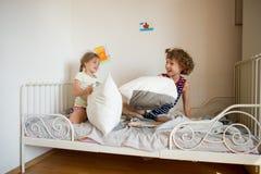 Le petit frère et la soeur ont présenté un combat d'oreiller dans la chambre à coucher image libre de droits