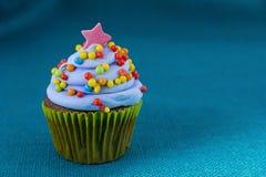 Le petit gâteau avec le givrage de myrtille et coloré arrose Photo stock