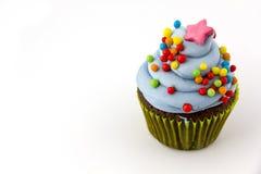 Le petit gâteau avec le givrage de myrtille et coloré arrose Photographie stock
