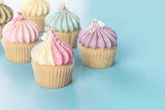 Le petit gâteau coloré d'arc-en-ciel a placé sur la tonalité en pastel bleue Image stock