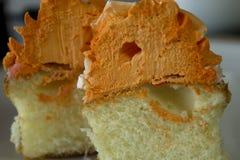 Le petit gâteau de vanille a complété avec le givrage orange et blanc Photo libre de droits