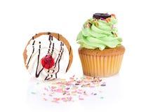 Le petit gâteau et les un bon nombre blancs et verts de coloré arrose Images libres de droits