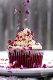 Le petit gâteau rouge de velours dans la neige avec le coeur arrose Photos libres de droits