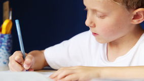 Le petit garçon écrit diligemment son travail clips vidéos