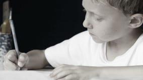 Le petit garçon écrit diligemment son travail : style noir et blanc banque de vidéos