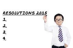Le petit garçon écrit ses résolutions en 2015 Photo libre de droits