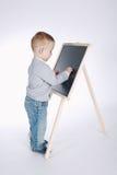 Le petit garçon écrit sur le tableau noir Image stock