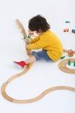 Le petit garçon établit la barrière pour le chemin de fer en bois Photographie stock libre de droits