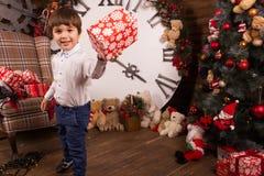Le petit garçon adorable présente un cadeau de Noël Vacances de famille images libres de droits