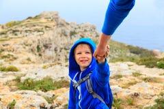 Le petit garçon a aidé par le parent sur augmenter en montagnes Photos stock