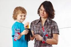 Le petit garçon aide sa mère à arrêter vers le haut votre gant et chaussettes photos libres de droits