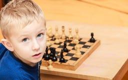 Le petit garçon apprennent à jouer aux échecs Images stock